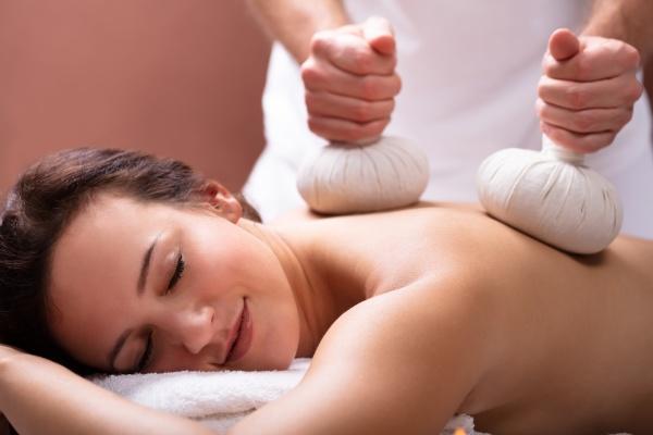 terapeut giver massage med naturlaegemidler komprimere