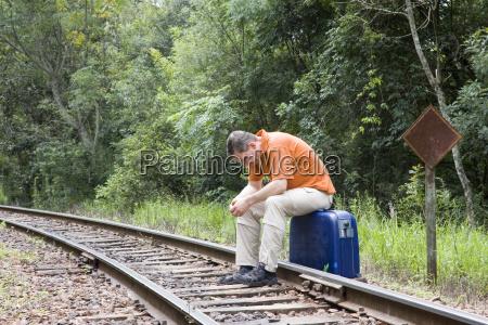 mand sidder pa kuffert pa spor