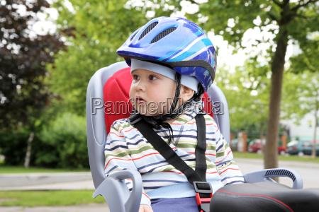barn sidder pa cykel i styrthjelm