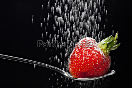icing sugar falling on a strawberry