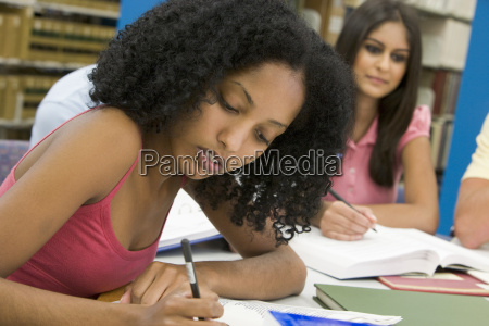 fire mennesker i biblioteket studerer