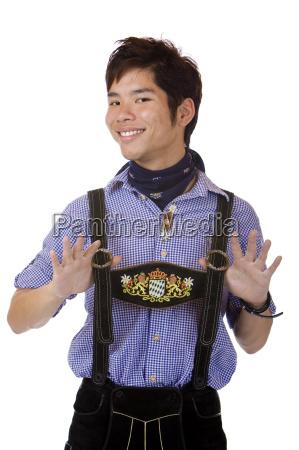 ung asiatisk i bayersk oktoberfest laederbukser