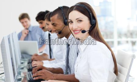 forretningskvinde med headset pa smilende ved