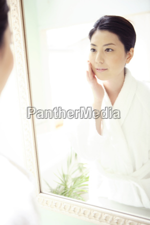 woman looking at herself in a