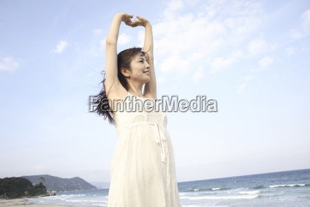 japanese woman stretching on a beach