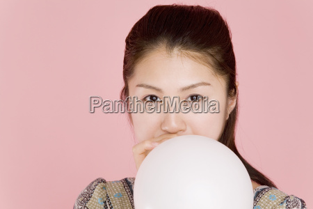 japanese young woman blowing up a