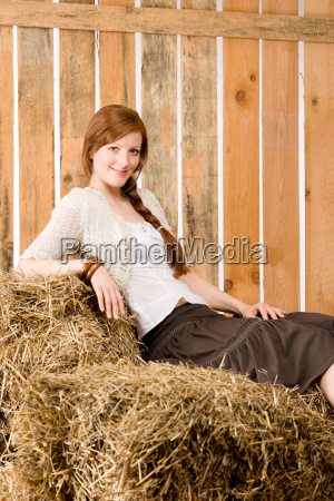 romantic young woman sitting on bales