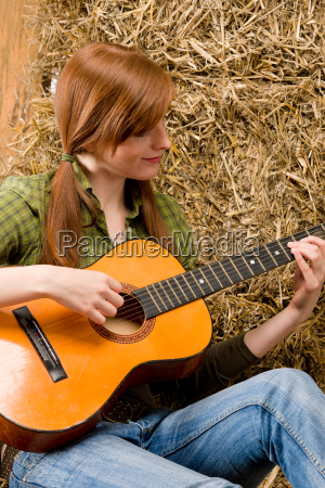 young country woman playing guitar in