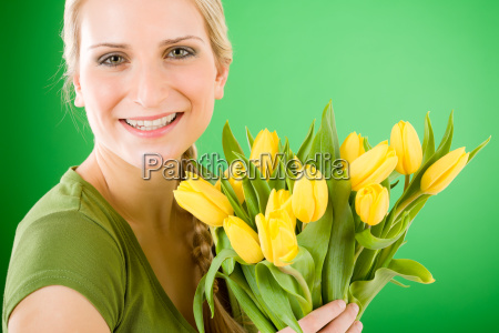 young happy woman hold yellow tulips