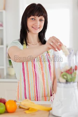good looking brunette woman putting vegetables