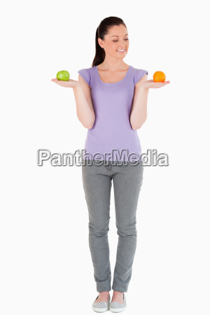good looking woman holding fruits while