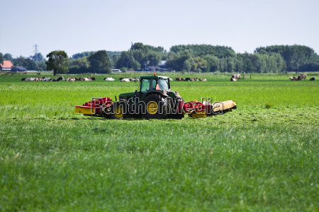 farmer on tractor mowing grass in