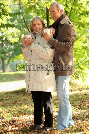older couple outdoors with hot drinks