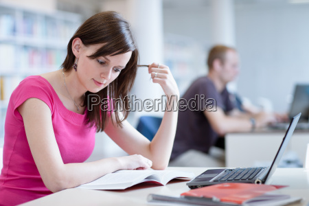 kvindelig studerende med laptop og boger
