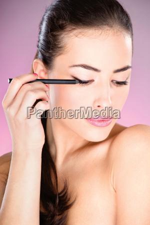 kvinde anvender kosmetiske blyant pa ojet