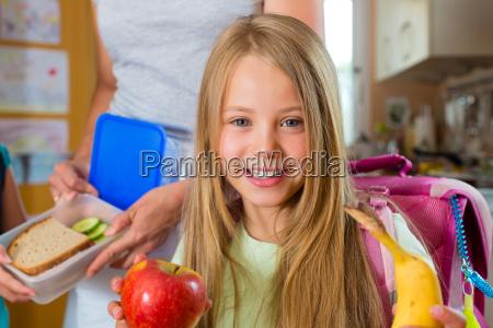 family mother makes breakfast for school