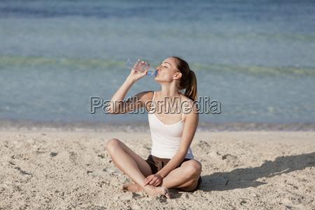 kvinde drikkevand fra en flaske pa
