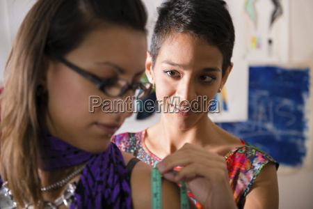 fashion designer using measuring tape with