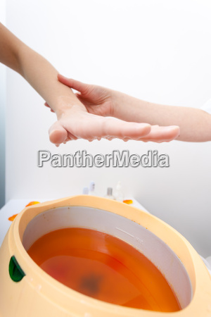 female hand and orange paraffin wax