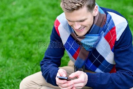 happy smiling man using mobile phone