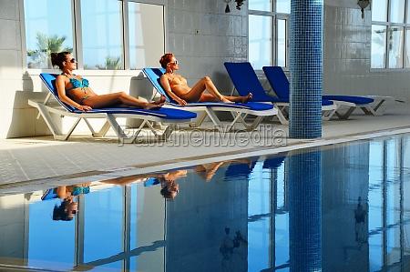 to unge kvinder ved swimmingpoolen