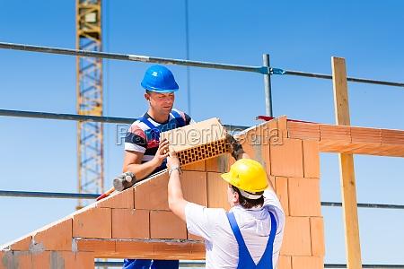 to bygningsarbejdere pa en byggeplads
