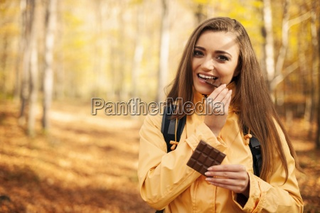 happy young hiker woman eating chocolate