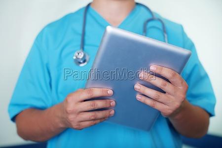doctor working on digital tablet