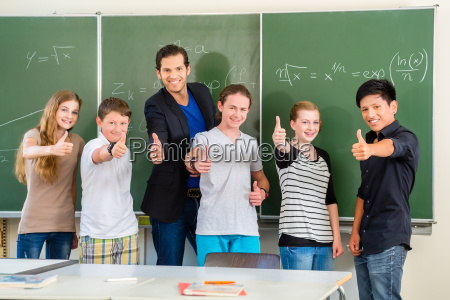 laerer med elever i skole foran