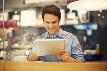 smiling man using digital tablet in