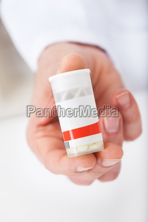 doctor holding a pill container at