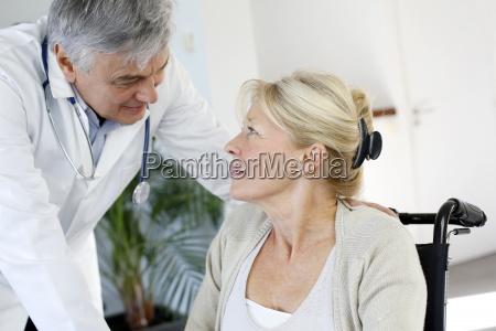 portraet af kirurg taler til patient