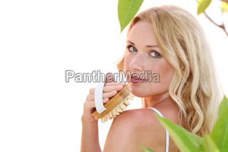 smuk blond kvinde med massage borste