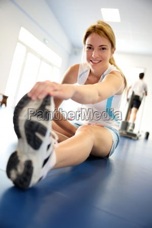 kvinde straekker sig ud i gym