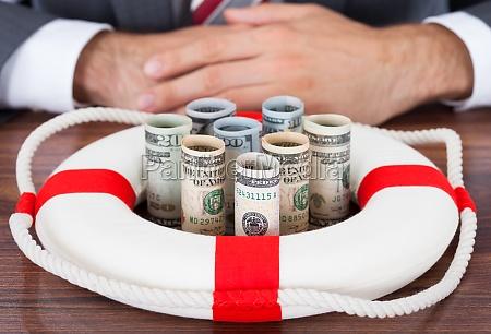 forretningsmand beskyt valsede bank noter med