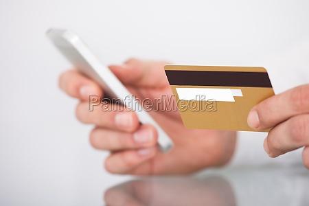 mand shopping med kreditkort og mobiltelefon