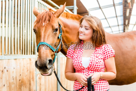 woman leading pony in stables