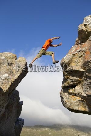 mand rock climber hoppe mellem klipper