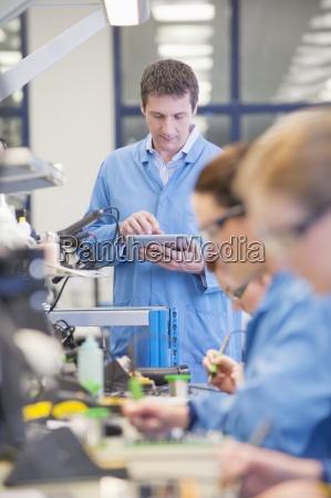 tilsynsforende med digital tablet produktionslinje i