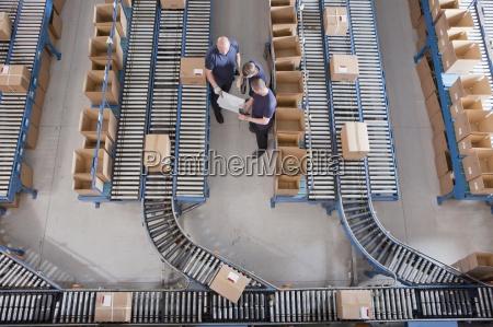 arbejdere mode blandt kasser pa transportband