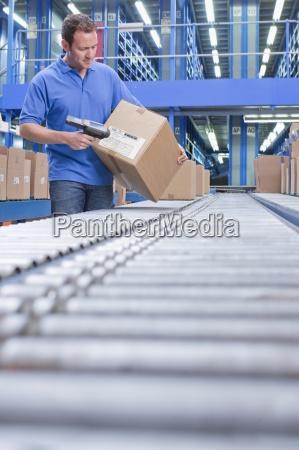 worker med stregkodelaeseren scanning boksen transportband
