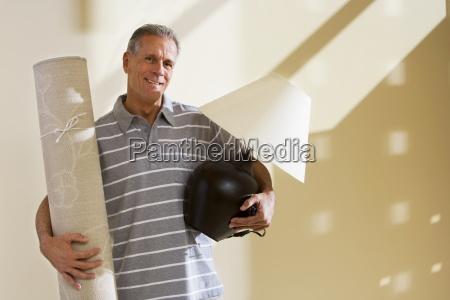 senior mand transporterer oploftet taeppe og