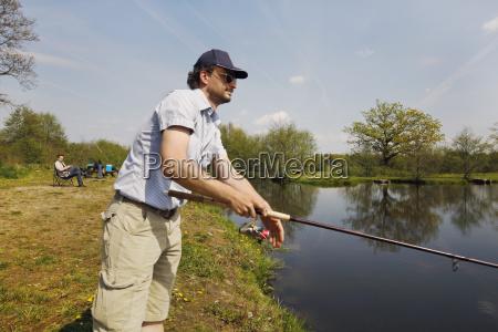 fisker med stang i handen