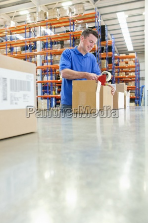 worker taping cardboard boxes on production