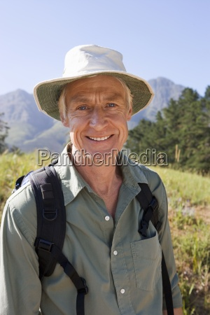 senior man with rucksack and sun