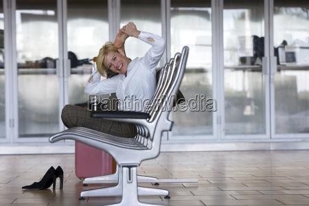 forretningskvinde straekning i lufthavnen venter omrade