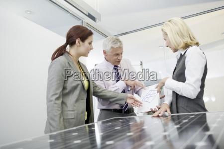 tre erhvervsfolk diskuterer solpanel teknologi