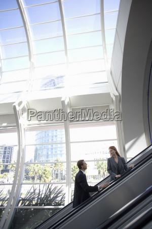 forretningskvinde og forretningsmand stigende rulletrappe side