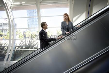 forretningskvinde og forretningsmand stigende rulletrappe smil
