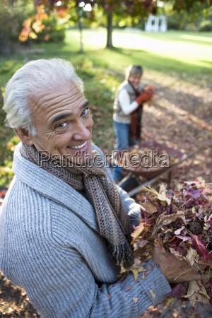 senior par indsamling efterarsblade i trillebor